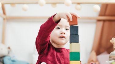 Kleuter die met blokken speelt en spelend leert
