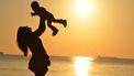 Moeder die haar kind in de lucht teilt tegen een ondergaande zon en geniet van het moment
