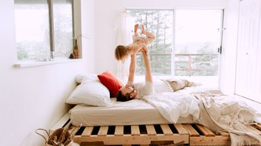 middagslaapje peuter / vader speelt met kind op bed