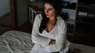 Vrouw zit met gekruisde armen op bed, genoeg van mensen om haar heen