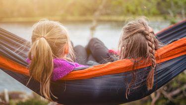 twee kinderen liggen in de zon in ean hangmat