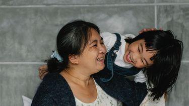 Oma en kleindochter lachend en knuffelend