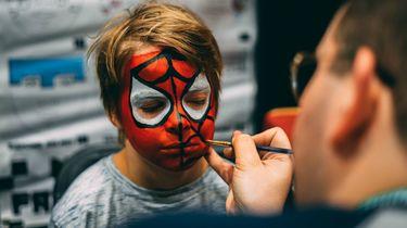 jongetje wordt geschminkt als spider man voor carnaval