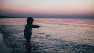 Kind met het sterrenbeeld waterman die in de zee staat