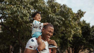 Vader met kind op de schouders