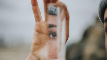 iemand kijkt nara zichzelf in een spiegelscherf