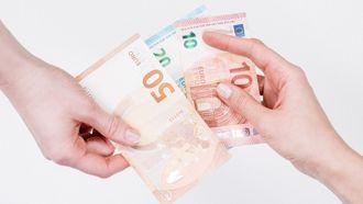 financieel misbruik / twee handen houden briefgeld vast