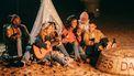 Vriendengroepje zit gezellig rond een kampvuur. Woorden die je niet in Engels kunt vertalen