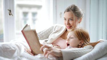 Moeder is een boek aan het voorlezen aan haar zoon in bed