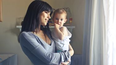 Moeder die kind draagt op linker heup