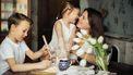 Moederdie met haar kinderen aan tafel zit en die hen leugens vertelt