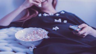 Vrouw die op de bank ligt en popcorn eet bij een Feel good film