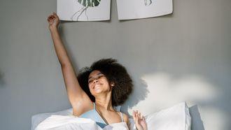 Vrouw die heel blij wakker wordt omdat ze calorieën heeft verbrand met slapen