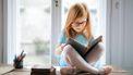 Roodharig meisje zit met een grote bril in kleermakerszit een boekje te lezen: een van de goede gewoonten die een kind kan aanleren