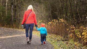 Moeder loopt hand in hand met zoontje en praat met hem over modder