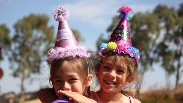Twee meisjes met feestmutsen op en een ballon die een kinderfeestje vieren