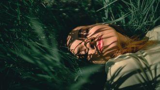vrouw ligt met hoofd in het gras