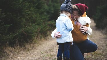 Moeder met baby in draagzak die haar peuter omhelst, omdat zij behoefte heeft aan een beetje oxytocine