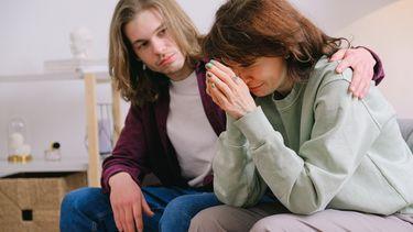 Vrouw zit huilend op de bank en man troost haar. Tips om iemand te troosten
