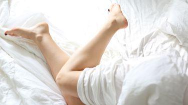 masturberen / vrouw ligt in bed met blote benen
