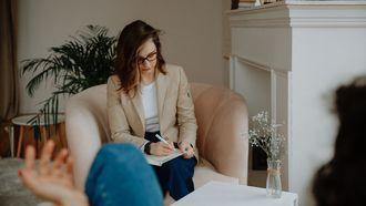 Therapeut die met een vrouw praat en aantekeningen maakt