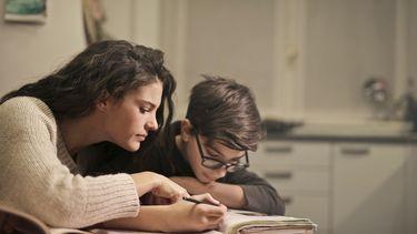 Moeder die haar zoon helpt bij het huiswerk