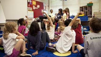 Kinderen op de opvang die zich goed gedragen en hun vinger opsteken om iets te vragen