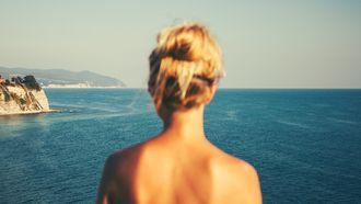 vrouw staat voor de zee