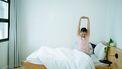 Vrouw rekt zich uit in bed, en voelt de voordelen van een ochtendroutine