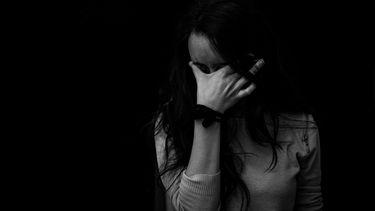 Vrouw die ontzettende stress heeft en haar hand voor haar ogen houdt