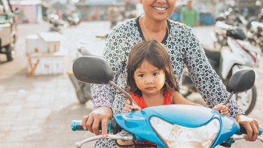 Moeder met haar kleuter op een scooter