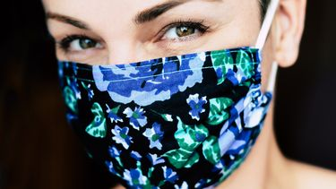 Vrouw met mondkapje dat ze zelf heef gemaakt en aan de richtlijnen van de overheid voldoet