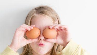 Meisje met eieren voor haar ogen die ze samen met haar ouders tot gezonde snacks maakt voor Pasen