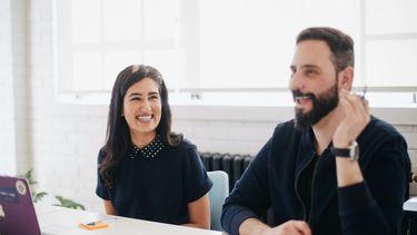 twee mensen op kantoor lachen samen en hebben geen sleur in hun werk