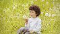 Jongetje van vier jaar oud in grasveld vol blaasbloemen