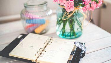 planner / agenda op tafel met vaas met bloemen
