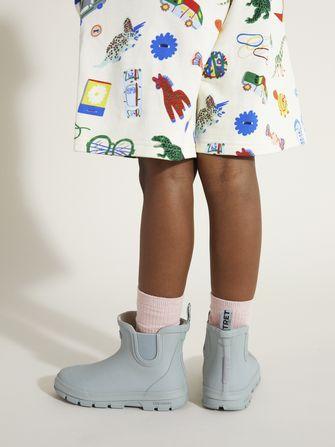 Kinderbeentjes in een korte broek en korte laarsjes van de collectie zomerkleren voor kinderen van Arket