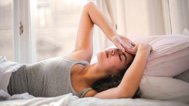 Vrouw die met een kater in bed ligt en dus niet de tips van deze anti-kater middeltjes gelezen heeft