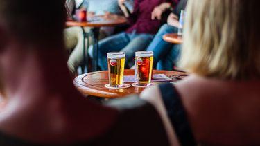 twee mensen zitten op een terras met twee biertjes