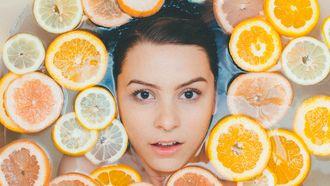 Gezicht van vrouw omringt door citroenen en grapefruit: Vitamine C voor je huid