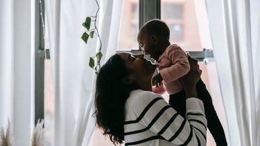 Single moeder die haar kind optilt