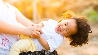 Gevoelig kind dat gekieteld wordt door moeder