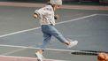Meisje dat tegen een voetbal trapt met kindersneakers aan