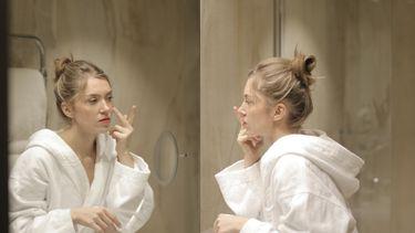 Vrouw die bij haar skincare routine bij acné fijne gezichtsverzorgingsproducten gebruikt