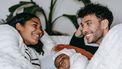 Ouders die trots naar elkaar kijken omdat hun baby tussen hen in slaapt