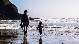 Moeder en kind die op het strand in de branding lopen