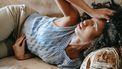 Vrouw ligt met buikpijn op de bank en is waarschijnlijk te vroeg ongesteld