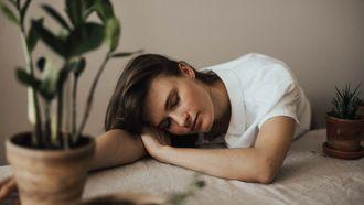goede nachtrust moe in de avond / vrouw ligt met hoofd op tafel