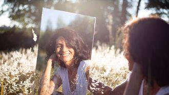 Vrouw kijk in de spiegel en heeft goede gewoontes