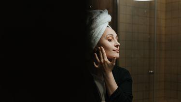 Vrouw die in de spiegel haar gezichtsverzorging doet omdat ze last heeft van droge en gevoelige huid en acné door haar mondmasker